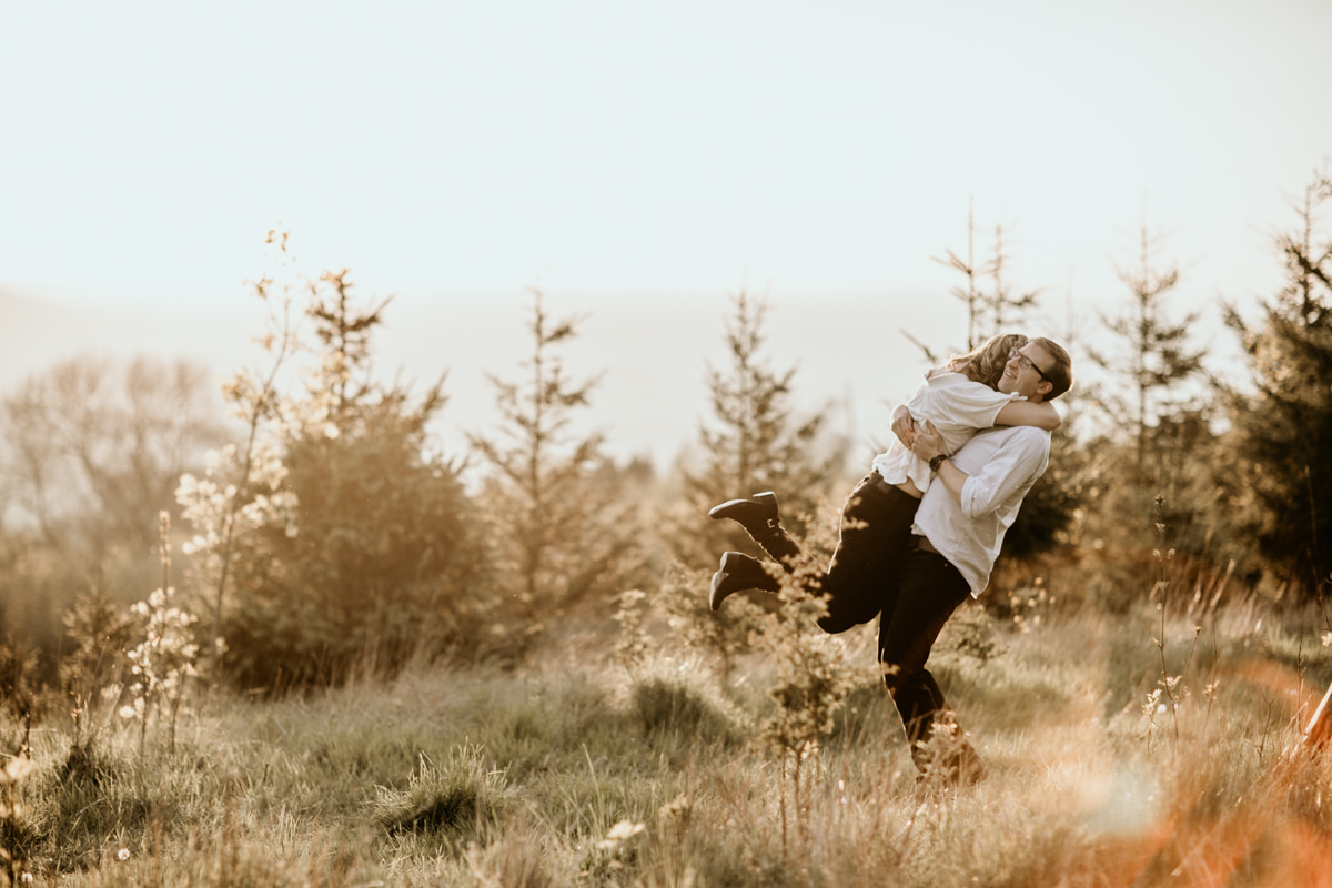 girl jumping in the arms of her fiance during the cotswolds countryside engagement session