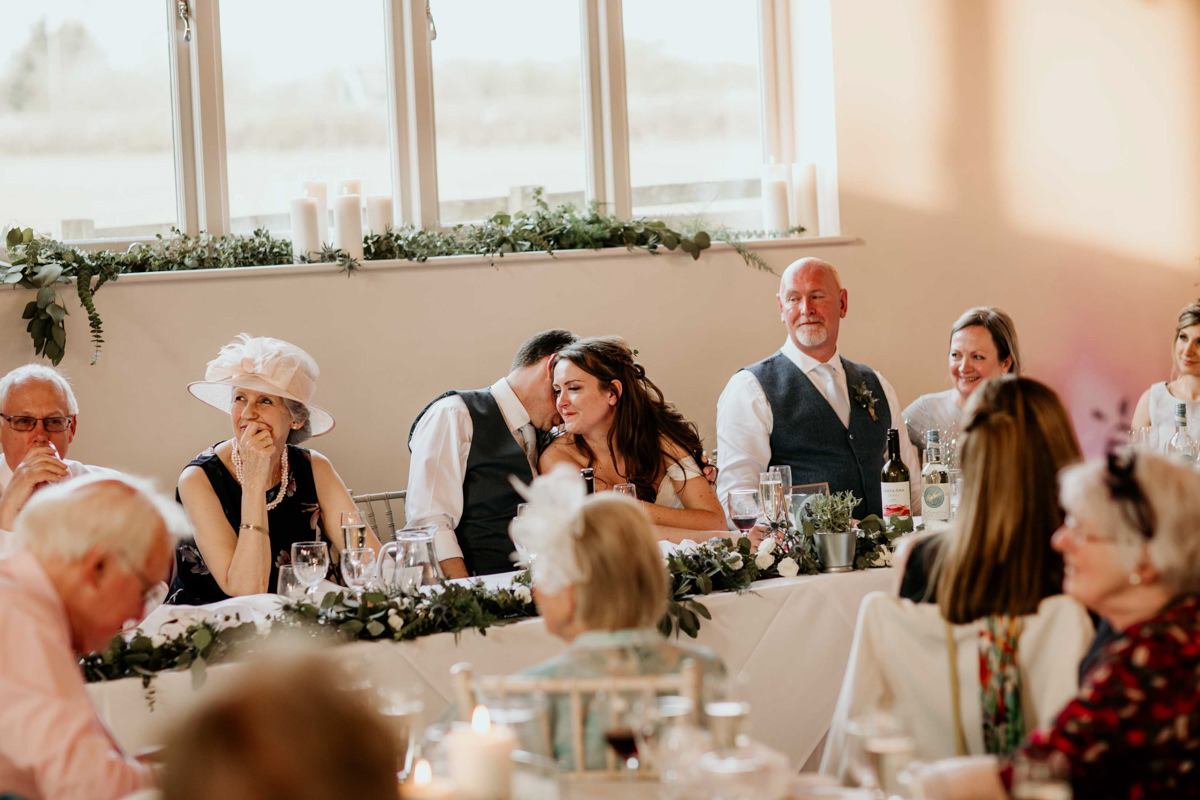 bride and groom kiss during wedding speeches at hyde house wedding venue
