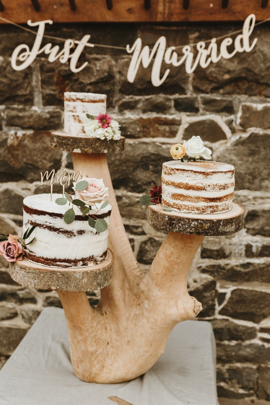 naked cake on a tree stomp for a boho wedding day