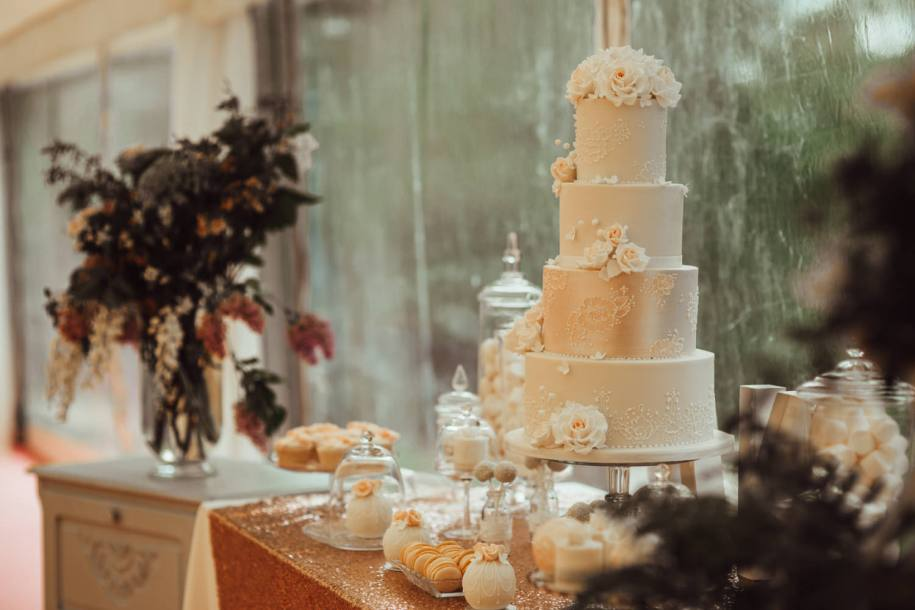 post blush wedding cake with embroidery and sugar roses for a desserts table