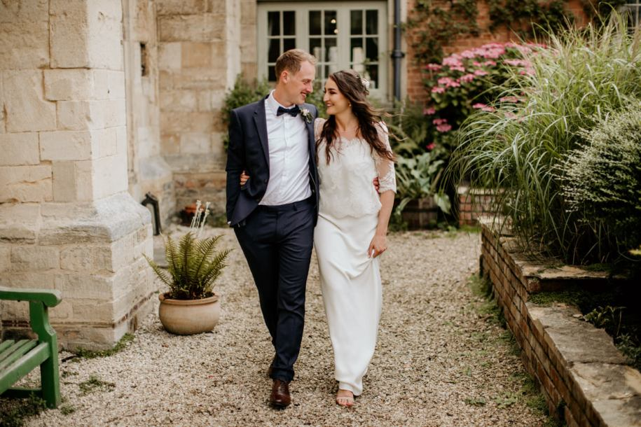 bride and groom walking during their bridal portraits at Priors Court Barn