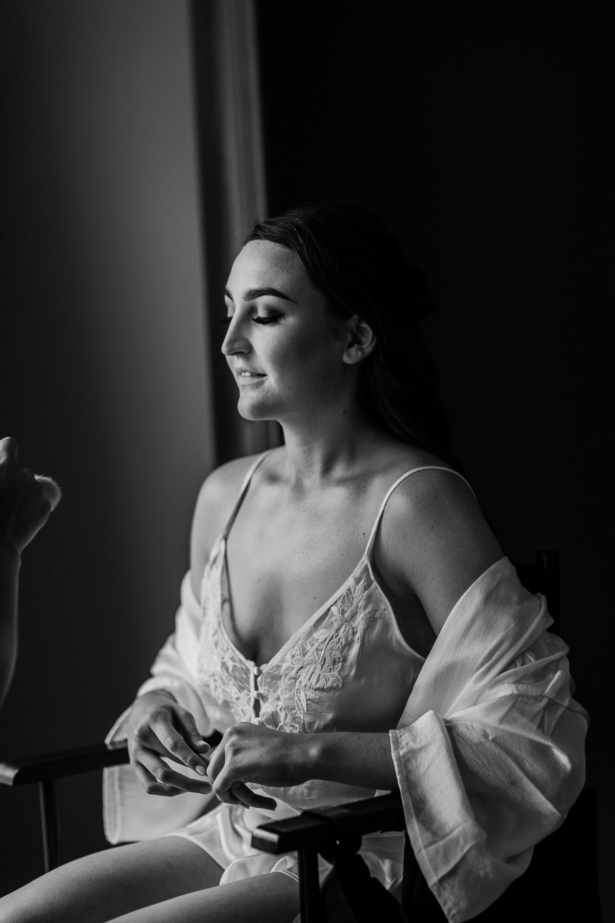 black and white image of bride getting make up done on the morning of the wedding day
