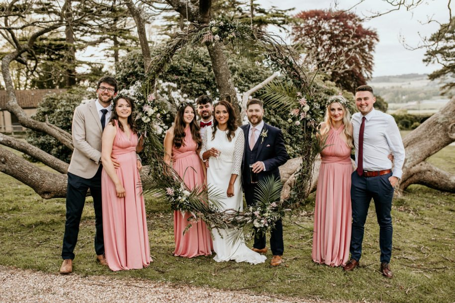 bridesmaids with bride and groom posing in front of a floral arch for family group shots