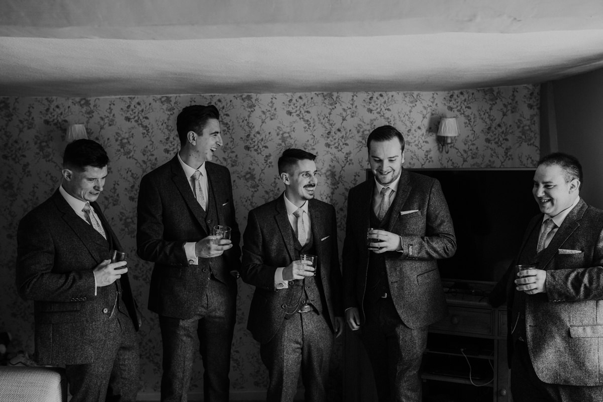 groom and groomsmen before the wedding ceremony having a drink