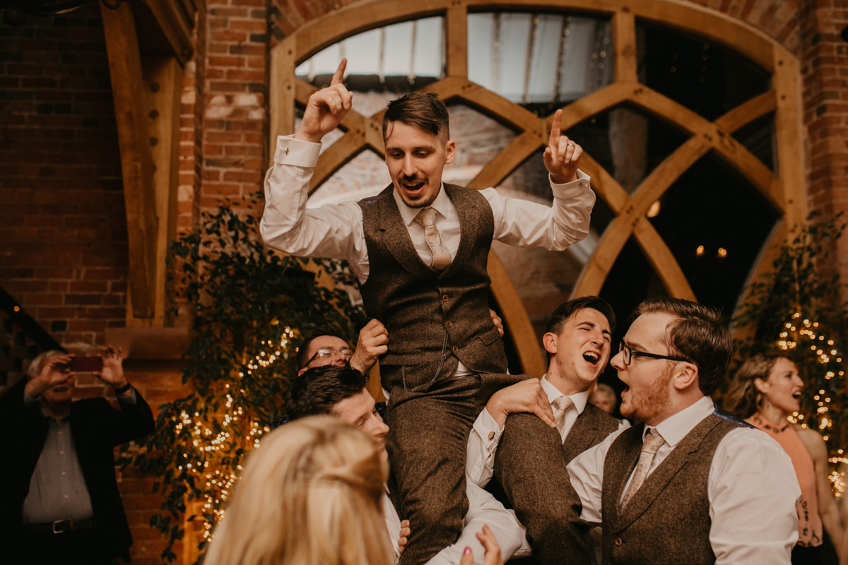 groom on friends shoulders at Shustoke Barn wedding venue reception