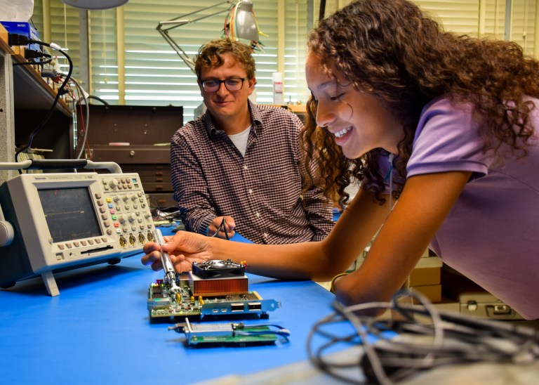 Luke Hawkins and Satori Chin inspect a circuit board