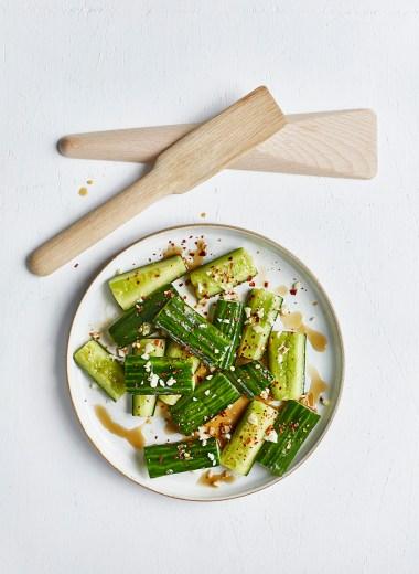 1. Vask agurken, og kutt av endene. Kutt den i fire like store deler, så du har fire «vedstubber», og del deretter hver del i to på langs, og deretter i to på langs igjen, så du sitter igjen med tykke agurkstaver. Legg dem med snittflaten ned på skjærefjøla, legg knivbladet mot skallet og trykk ned med den frie hånda. Skallet sprekker opp litt, og frøene knuses og fjernes fra agurken – det er meninga. Gjør det med alle agurkstavene. 2. Legg agurken, minus alle frøene som ligger igjen på fjøla, i en sikt eller et dørslag over en bolle. Strø over 1 ts salt og 1 ts sukker, og la det stå og renne av seg i minst en halvtime, eller opptil fire timer (da i kjøleskap). Ikke dropp dette punktet! 3. Bland sammen ½ ts salt, ½ ts sukker, riseddik, sesamolje og soyasaus i en liten skål, og visp til sukkeret og saltet er løst opp. Finhakk hvitløk, og legg til side. 4. Når agurken er ferdig avrent, rist godt på dørslaget så all væsken blir borte, og ha agurken over i en serveringsbolle. Hell over dressingen, og smak til med hvitløk og chiliflak. Strø over sesamfrø til slutt.
