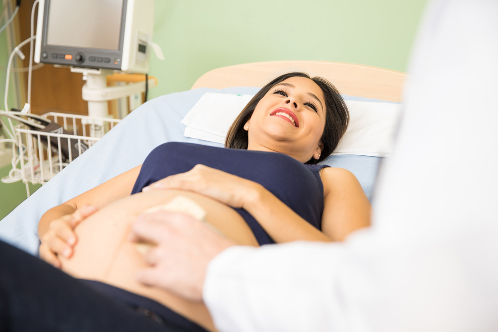 Smiling pregnant woman getting an ultrasound from her obstetrician