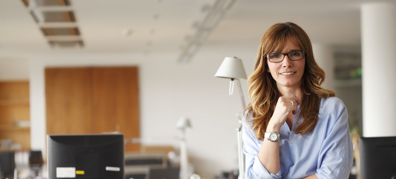 Middle aged woman with glasses smiling in her office