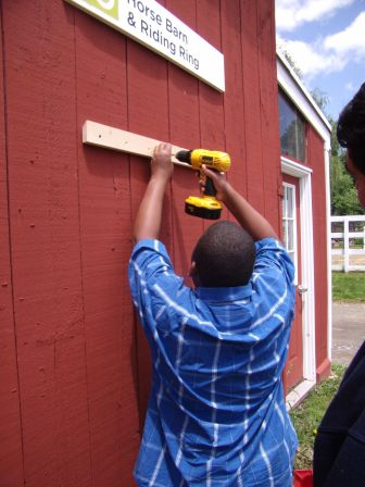 A student attaches the bracket to the barn, which will support the planter.