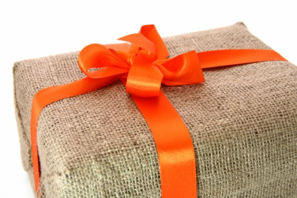 large gift box wrapped by burlap canvas with orange bow