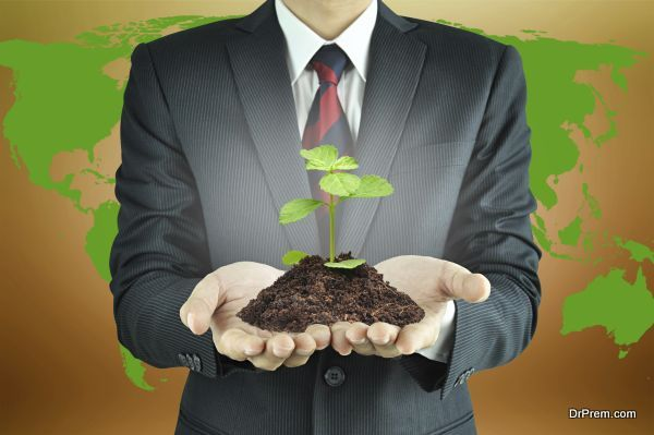 Businessman holding green seedling with soil