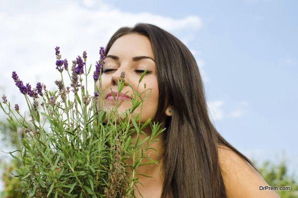 Beautiful woman in the garden smelling flowers.