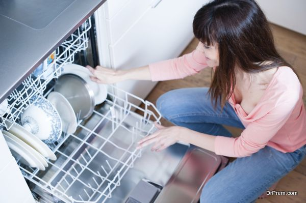 middle aged girl in the kitchen using dishwasher