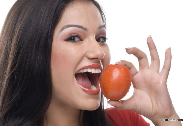 Woman about to eat a tomato