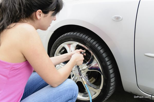 Young woman checking pressure and inflating car tires.