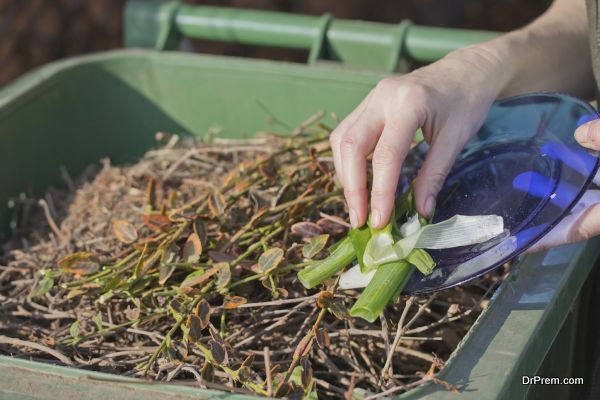 Woman hand is sacking of organic waste into a green bins