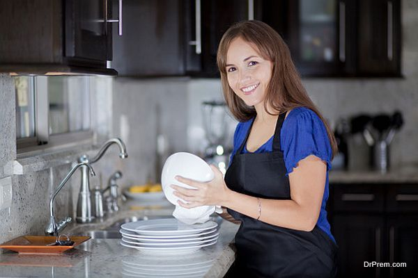 Cute girl drying dishes in the kitchen