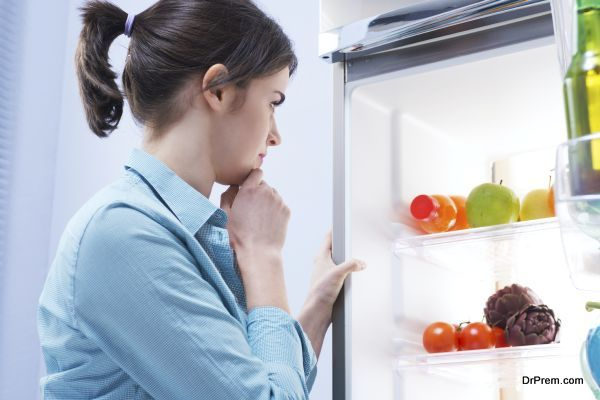 Young pensive woman looking in the refrigerator with hand on chin.