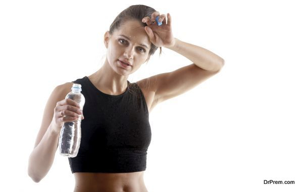Sporty yoga girl on white background holding a bottle of water, wiping sweat from forehead after practice