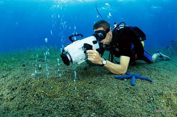 Scuba diver taking a photograph underwater
