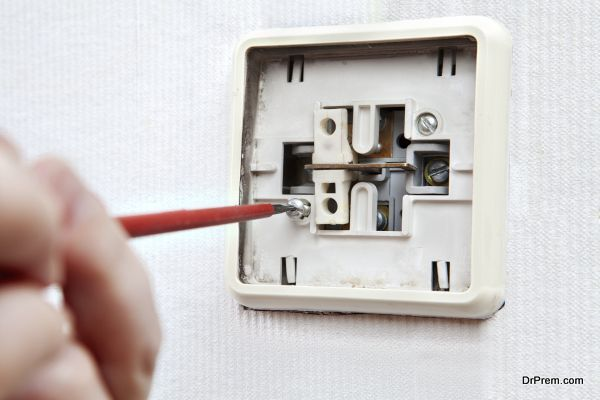 Renovated old light switch close-up, unscrewed bolt with screwdr