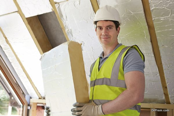 Builder Fitting Insulation Boards Into Roof Of New House