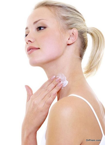 woman applying moisturizer cream on her neck