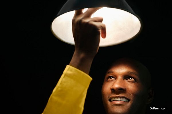 African man looking up and touching light bulb