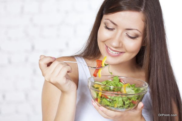 beautiful brunette woman eating salad