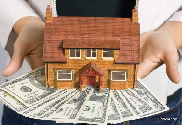 A person holding a miniature house and some dollar bills