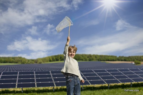 Portrait of boy holding up net to catch sunbeams in front of solar panels