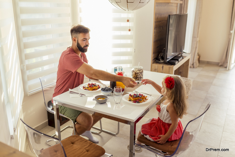 Young father and beautiful little daughter sitting at dinning room table, having breakfast