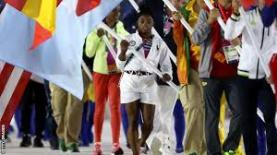 Simone Biles arrying flag