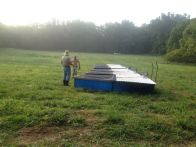 Morning chores, moving the pastured chickens to new grass before the humidity rises!