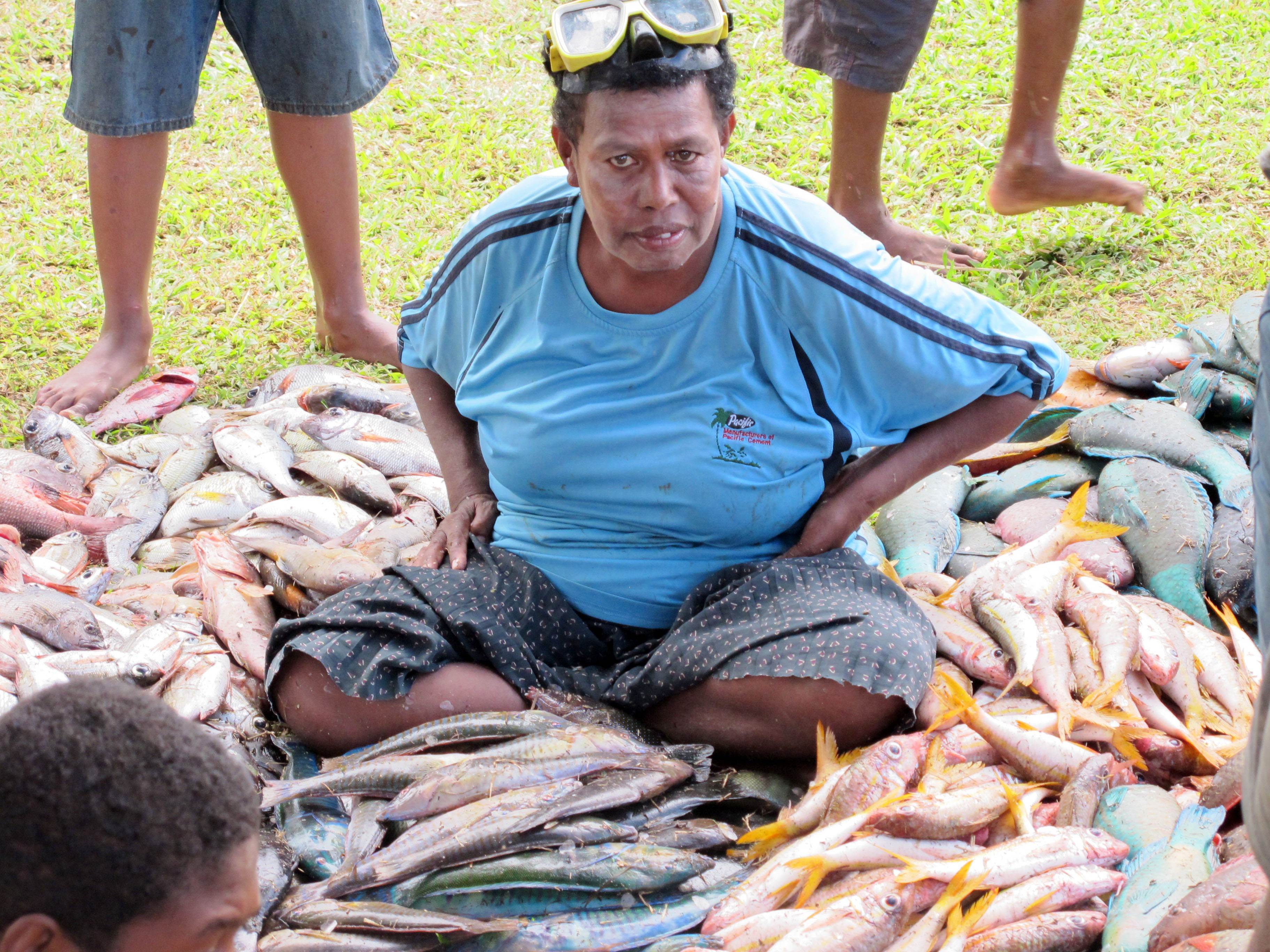 Woman surrounded by large catch from periodic harvest for a village church function in Fiji