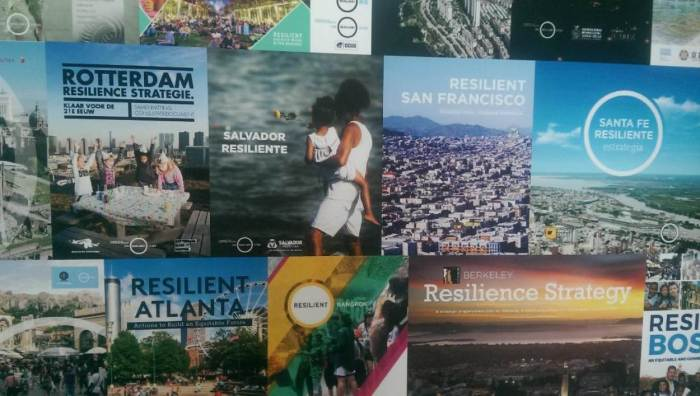 A an exhibition wall showing the covers of resilience strategies by members of the 100 Resilient Cities network in Rotterdam, July 9, 2019. Thomson Reuters Foundation/Megan Rowling