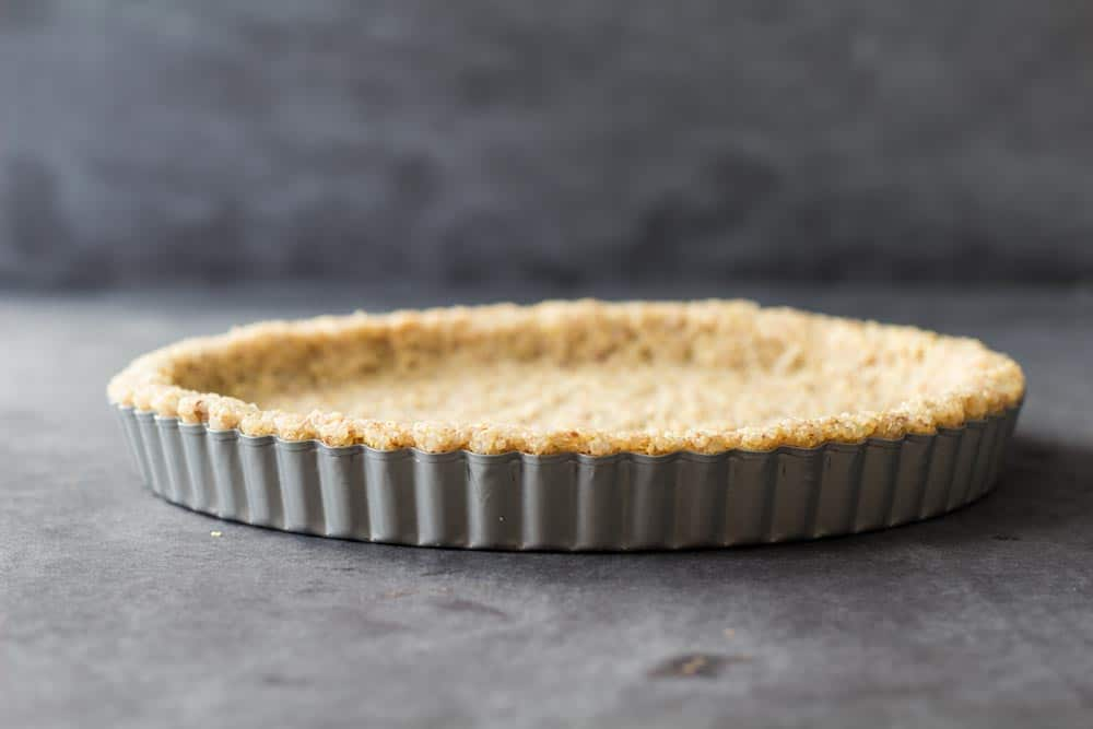 Uncooked 2-Ingredient Quinoa Crust in separable non-stick pie form suitable as quinoa quiche crust, quinoa pie crust and quinoa pizza crust.