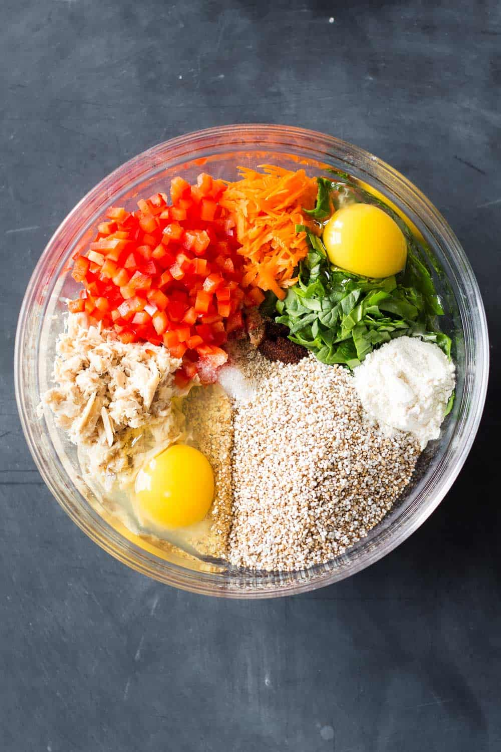 Ingredients for healthy Tuna Patties in a bowl. Puffed Amaranth, Eggs, Tuna, Chopped Bell Pepper, Grated Carrot, Chopped Baby Spinach, Flour, Chipotle Powder, Sea Salt, Pepper.