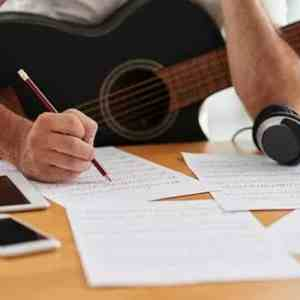 Songwriter with acoustic guitar and writing lyrics on a piece of paper.