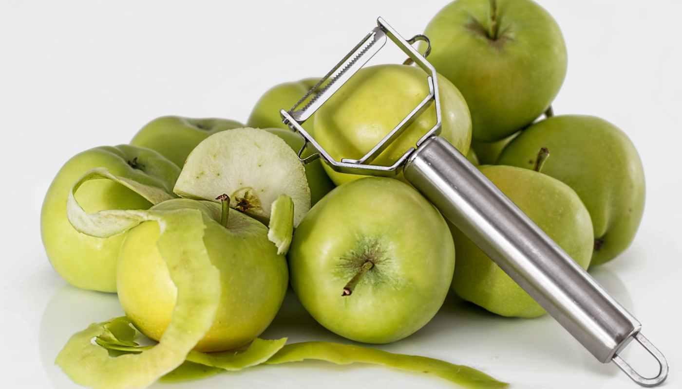 green unripe apple with silver peeler