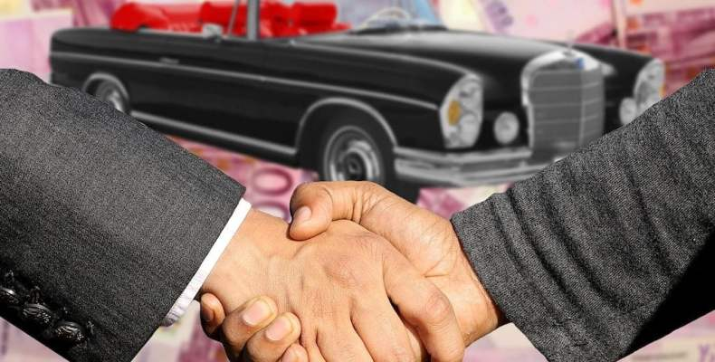 Shaking Hands in Front of Classic Car