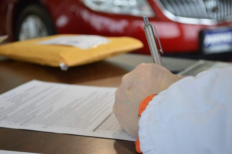 Contract Signing with Red Car in Background