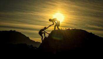 Climbers Pulling Each Other Up With Sun Behind