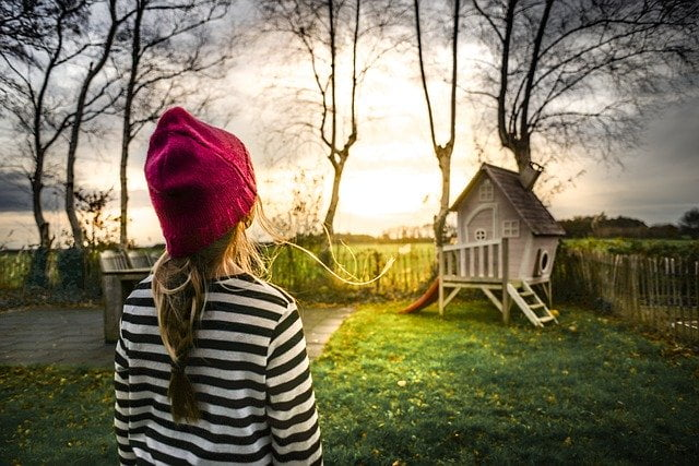 Girl Looking at Treehouse in Yard