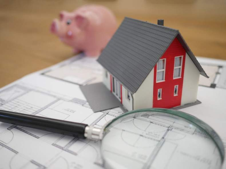 Model of House on Plans with Magnifying Glass and Piggy Bank