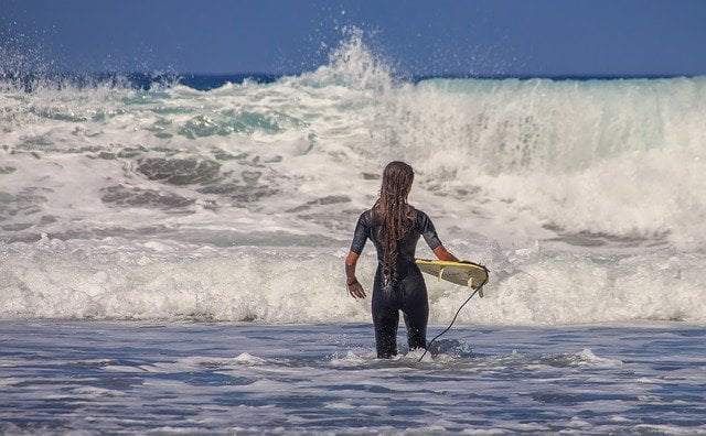 Woman Walking into Surf with Surfboard