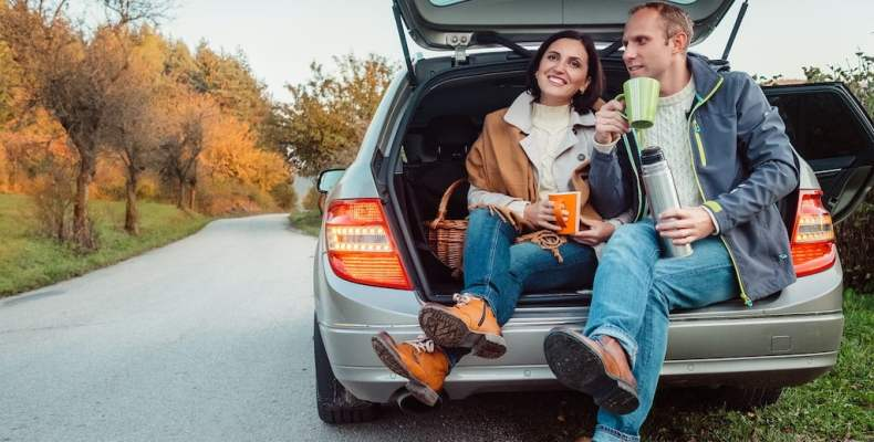 Couple Sitting In Hatchback Drinking Coffee