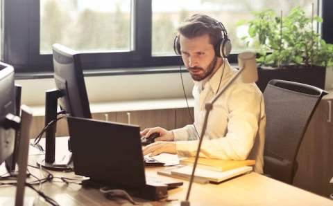 Man with Headset on Computer