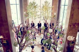 The elegant Social Lobby served as the ceremony site for this unique ceremony in the round, which provided a 360 degree vantage point and a more intimate experience. One of Katie's design visions for the wedding was to have indoor trees of some sort. So her father used the branches and trunks from some family Crepe Myrtle trees, salvaged after a tornado, to construct two 12-foot trees. He wrapped them in hammered patina copper, and they were later adorned with white LED lights and green and ivory yarn balls of various sizes.